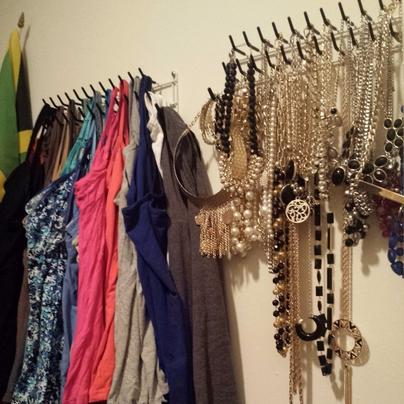 Reviewer photo of two of the racks on a wall, one with tank tops hanging from it and the other with necklaces and jewelry hanging from it