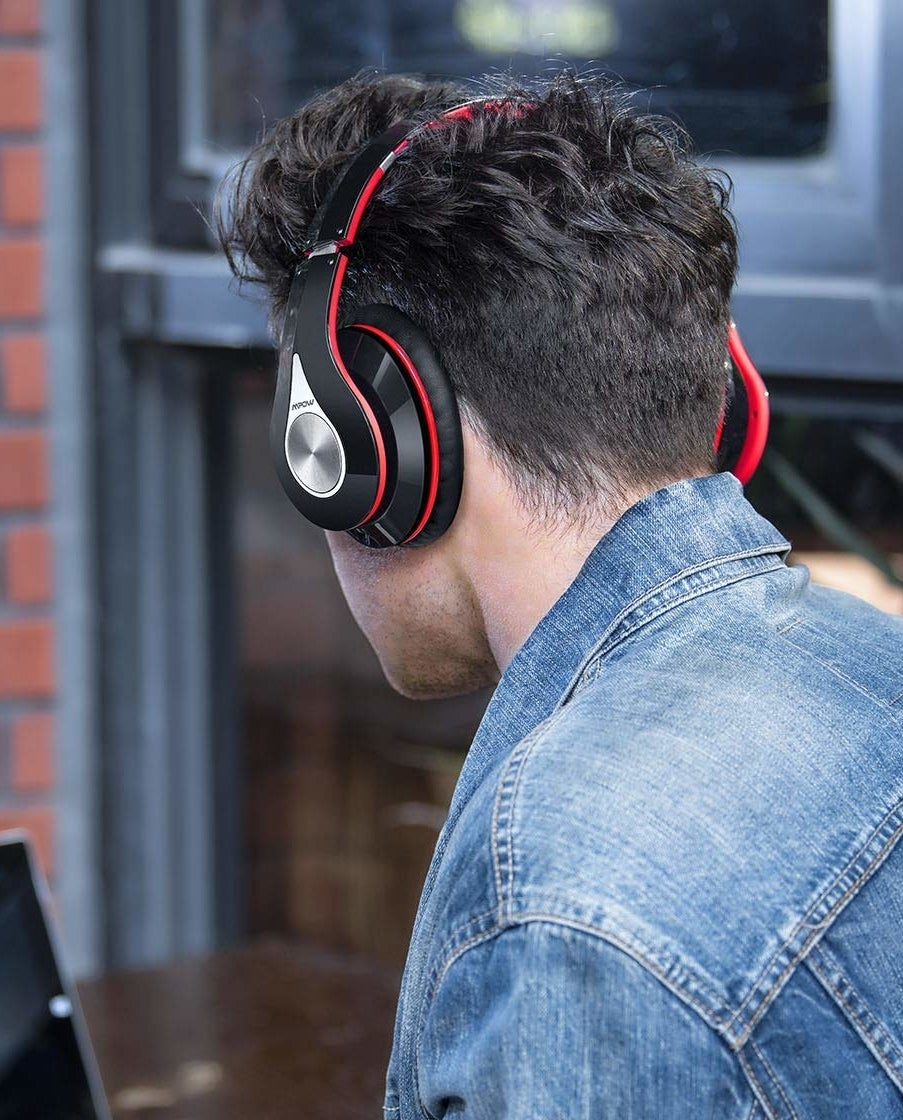 A model wearing the headphones in black and red