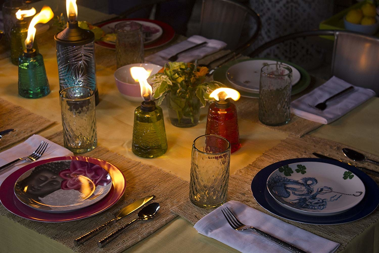 outdoor table setting at night with the colorful glass-size tiki torches lit