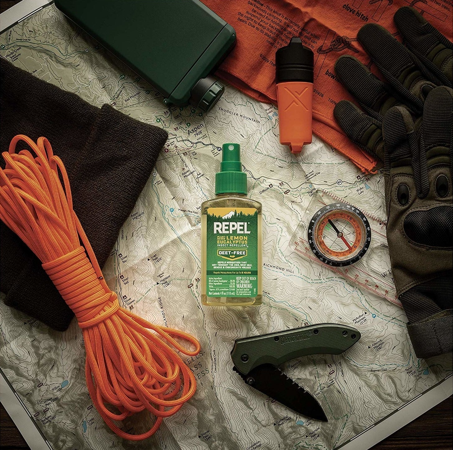 the spray on a map surrounded by other camping supplies like a compass and pocket knife