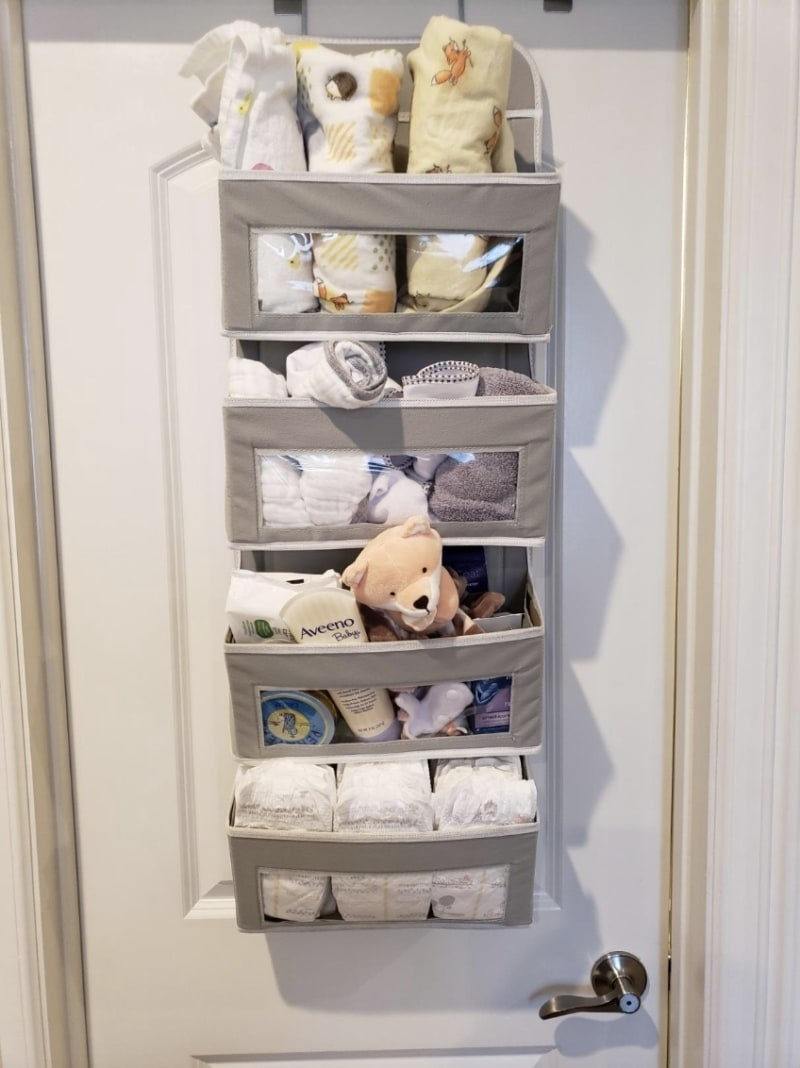 Reviewer photo of the organizer filled with baby products you can clearly see through the pockets