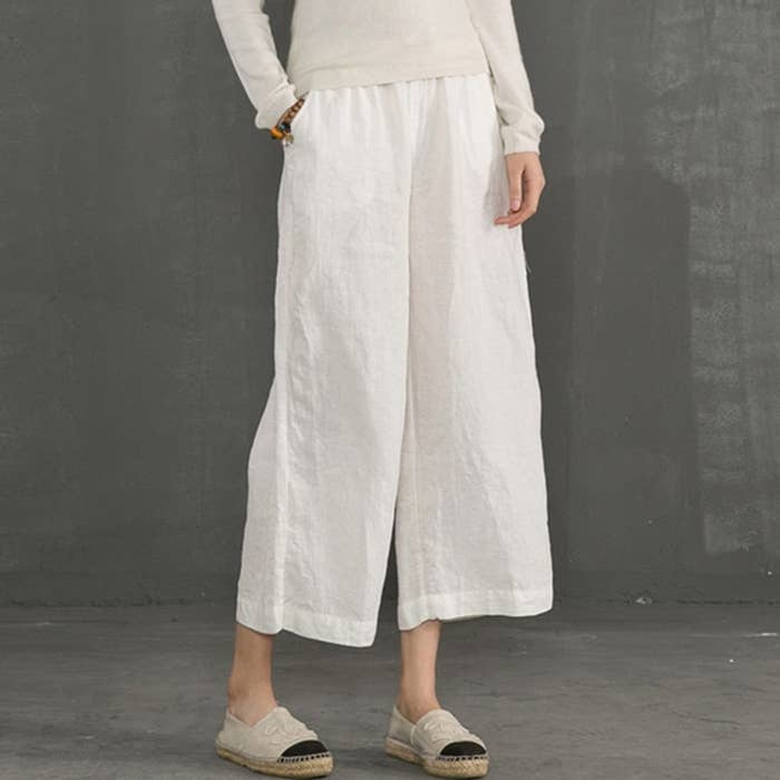 Model wearing the white mid-length pants with pockets on the side