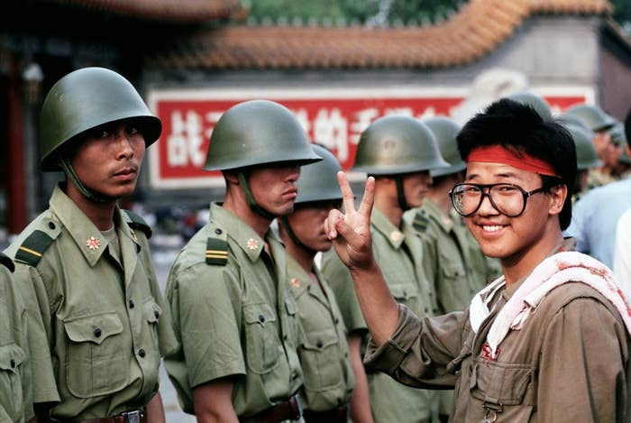 "A pro-democracy demonstrator gives the ""V for Victory"" sign to soldiers who are lined up, standing guard outside the Chinese Communist Party's headquarters."
