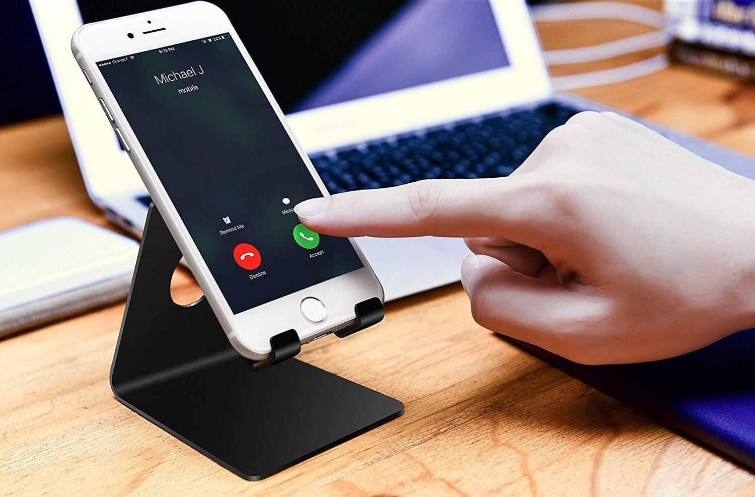 Cell phone stand in black with a phone in it on a desk