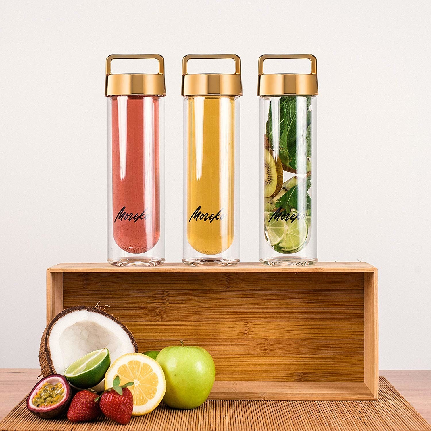 Three water bottles with gold lids, each holding a colorful drink and/or fruit