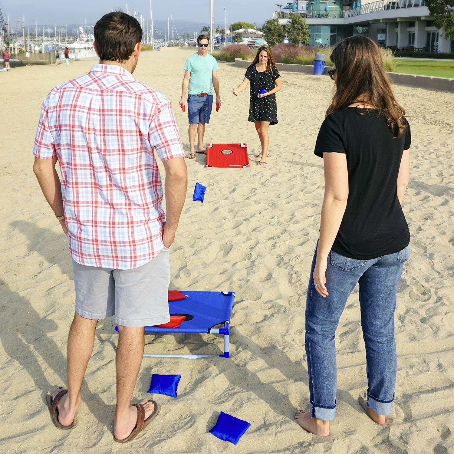 four people playing cornhole at the beach