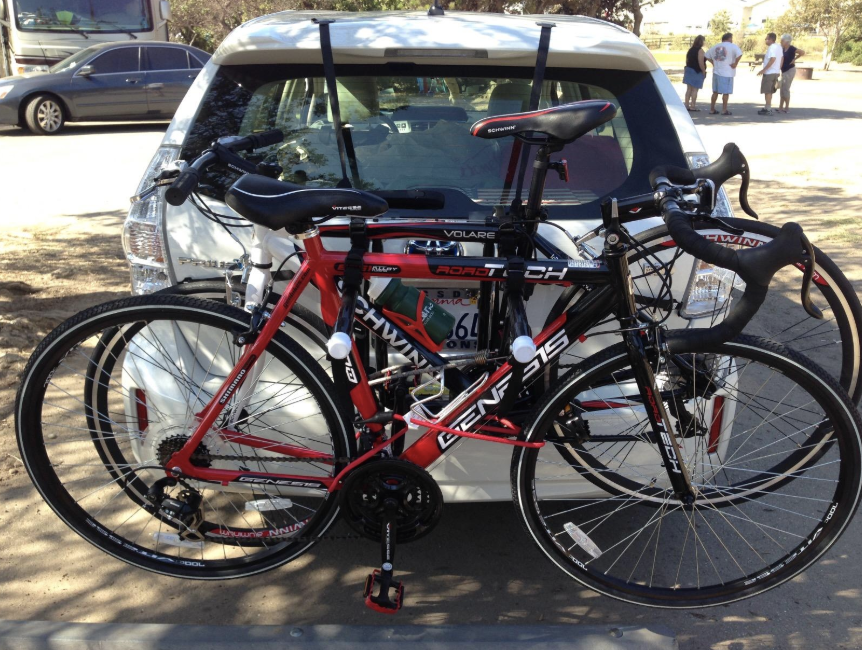 The back of a car holding up two bicycles using the rack