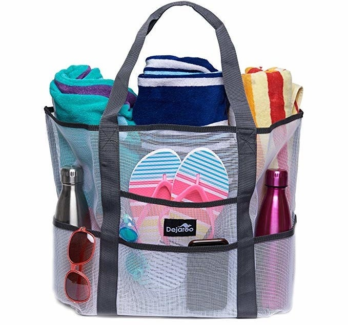 The tote holding flip-flops, two water bottles, sunglasses, three towels, and other items