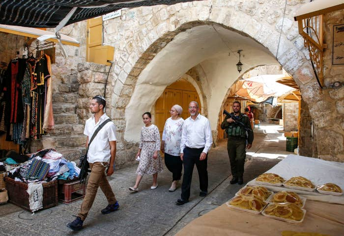 Jewish settlers guarded by Israeli security forces walk past Palestinian vendors' stalls and shops as they tour the Palestinian side of the old city market in the occupied West Bank city of Hebron.
