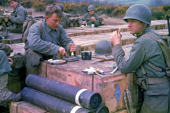 American combat engineers eat atop boxes of ammunition being stockpiled for the impending invasion.