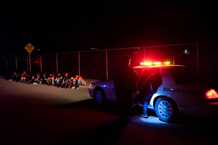 People are loaded into a squad car by a US Border Patrol agent after crossing the US–Mexico border into El Paso, Texas, just after midnight on June 1.