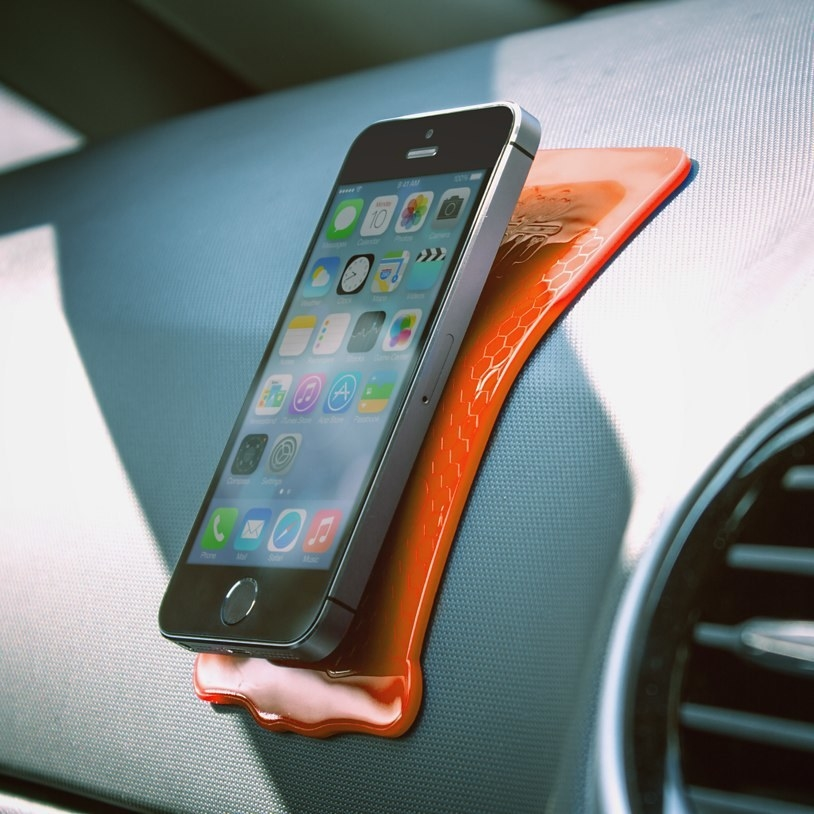 Picture of a phone attached to the grip strip on a car dashboard