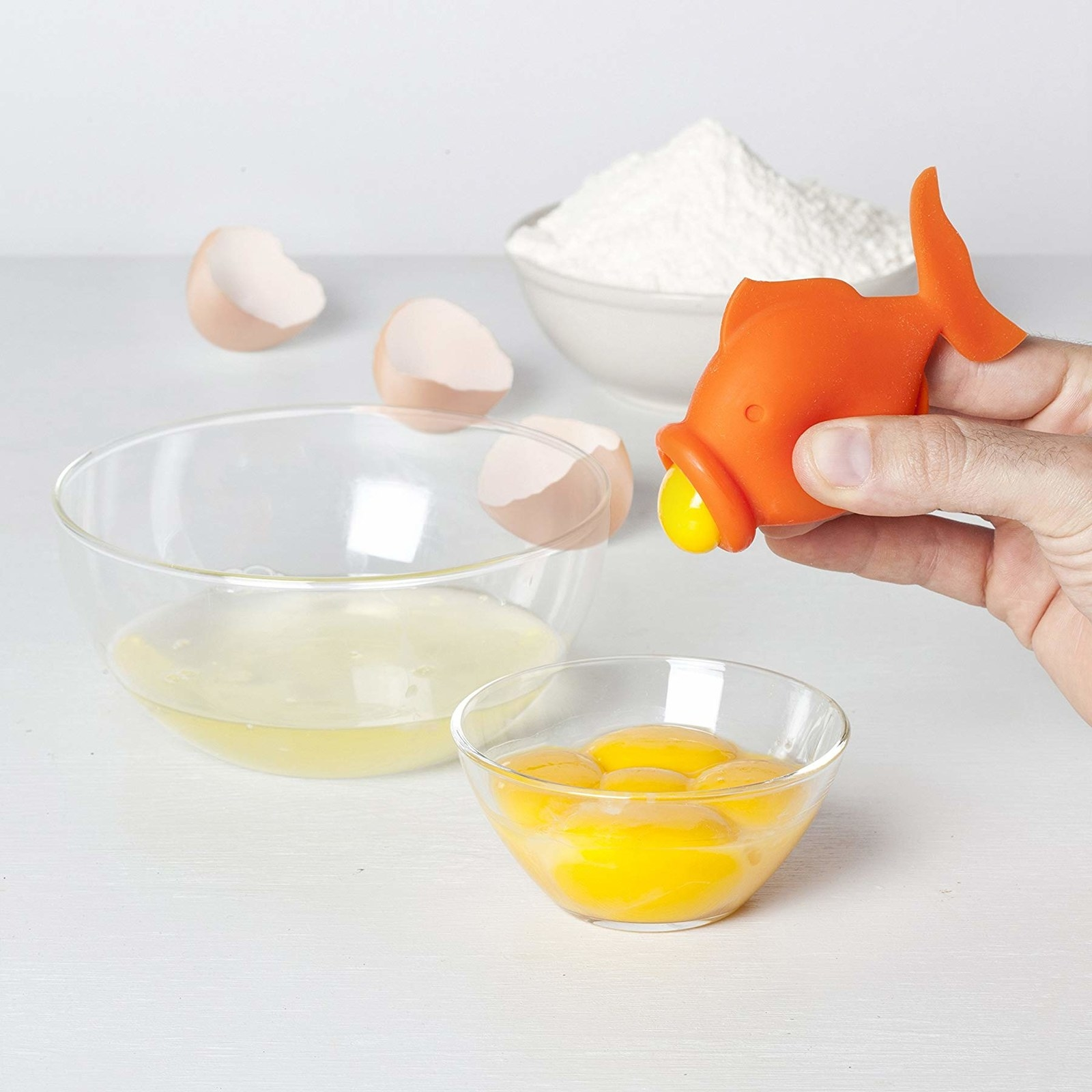 Hand squeezing egg yolk out of the fish-shaped egg separator