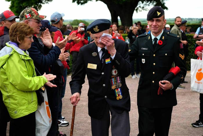 Richard Brown (center), a Canadian veteran of the World War II Battle of Normandy, departs with his son Andy to the applause of visitors following a commemorative ceremony in Normandy on June 5.