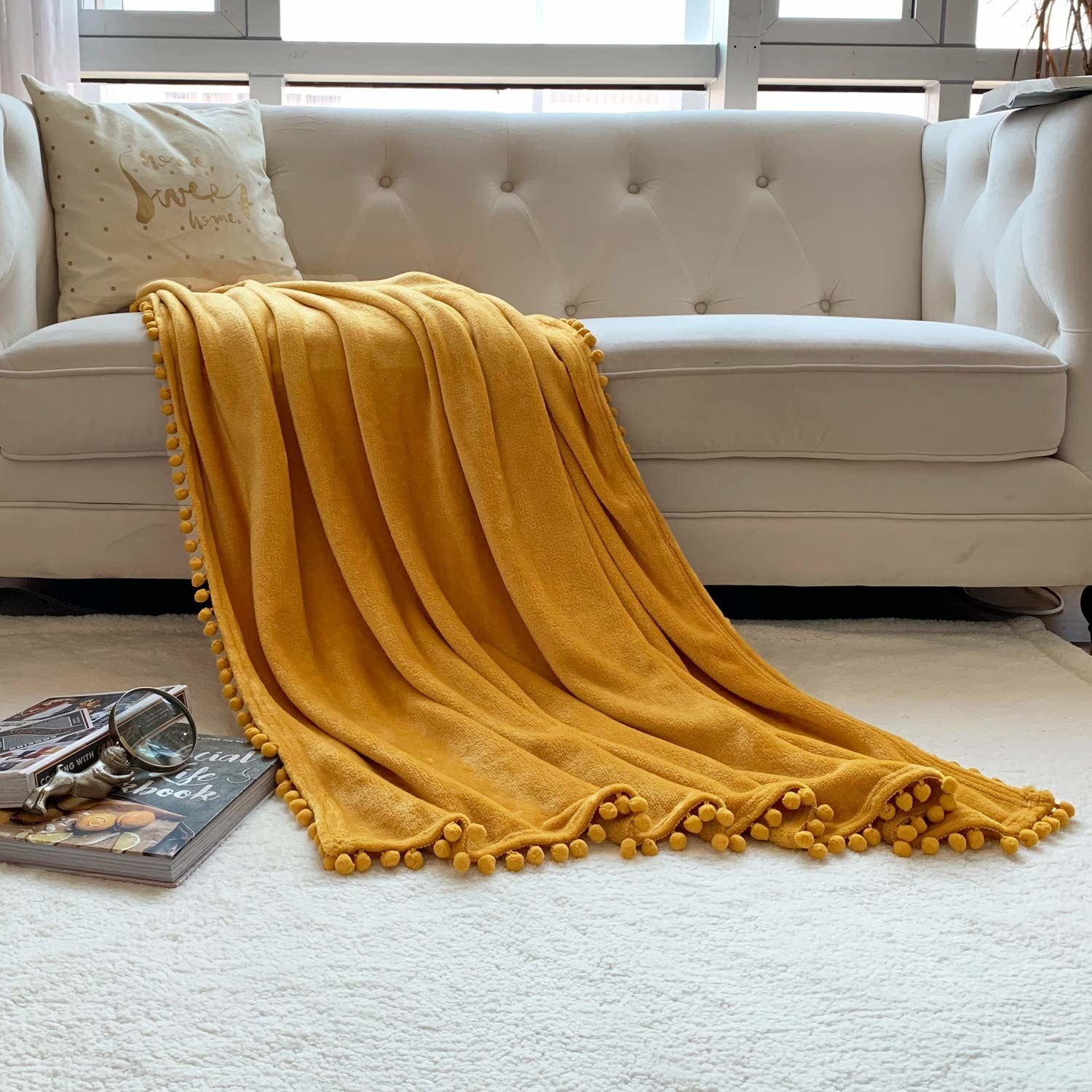 yellow blanket with pom pom trim on it thrown over a beige couch