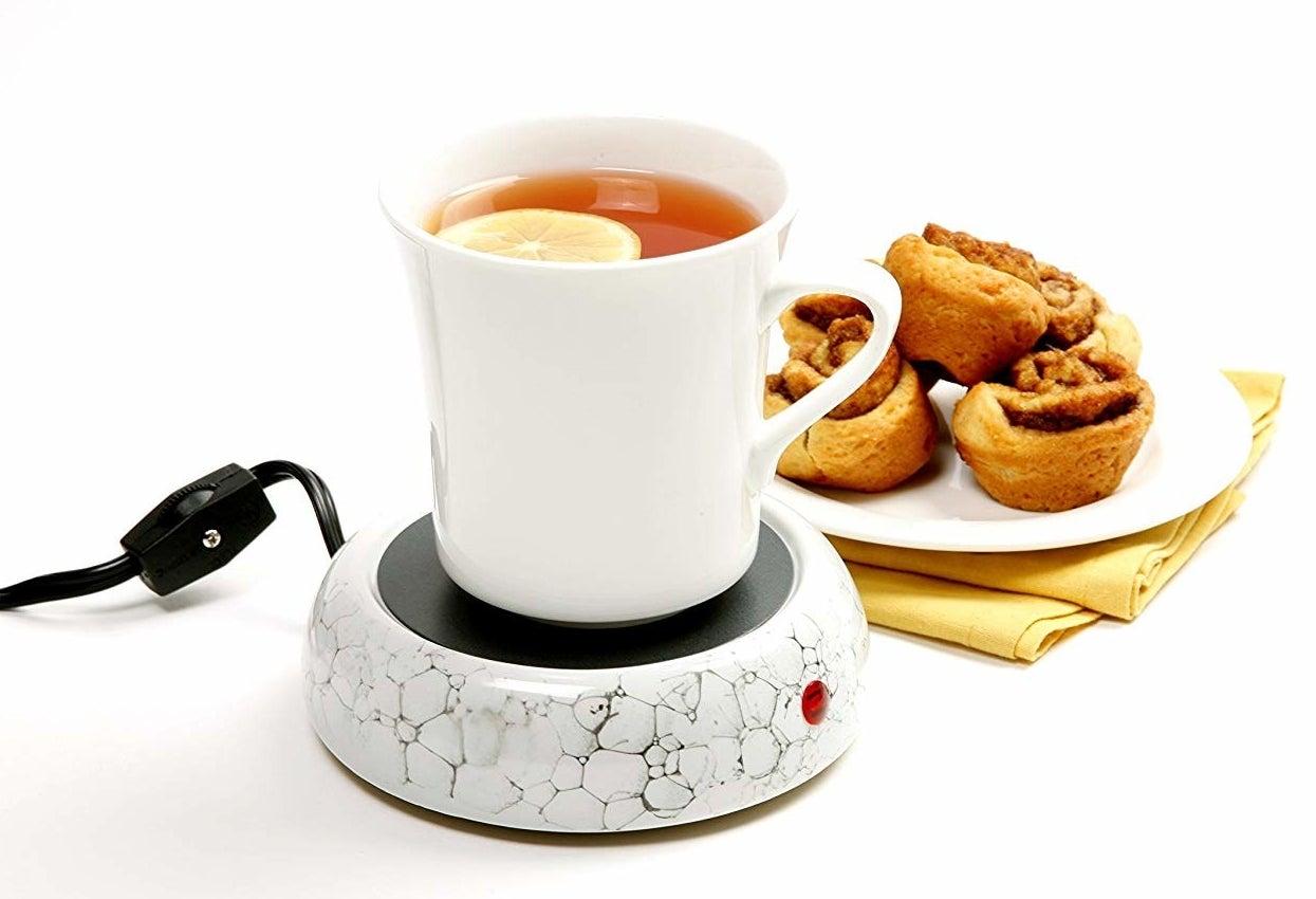 Mug of tea placed on ceramic mug warmer