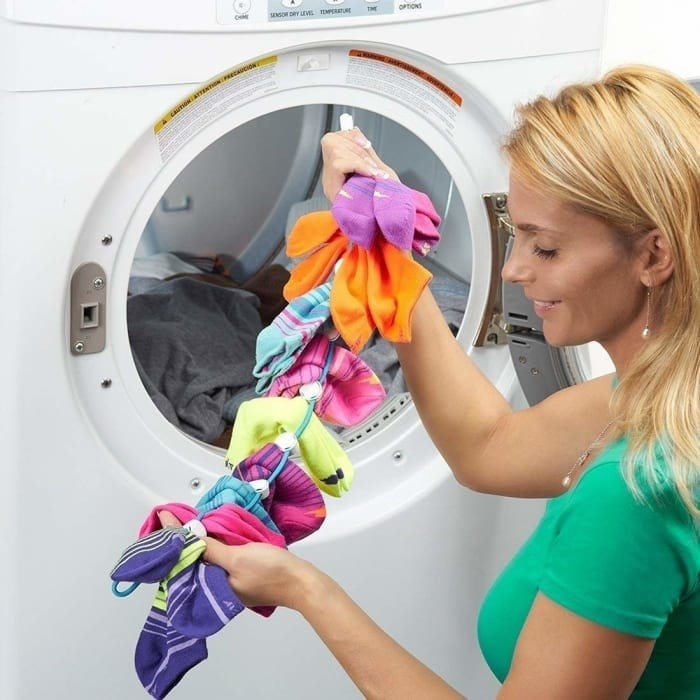 """Model sitting next to a dryer holding the """"sock dock"""" with tons of matching socks clipped to it"""