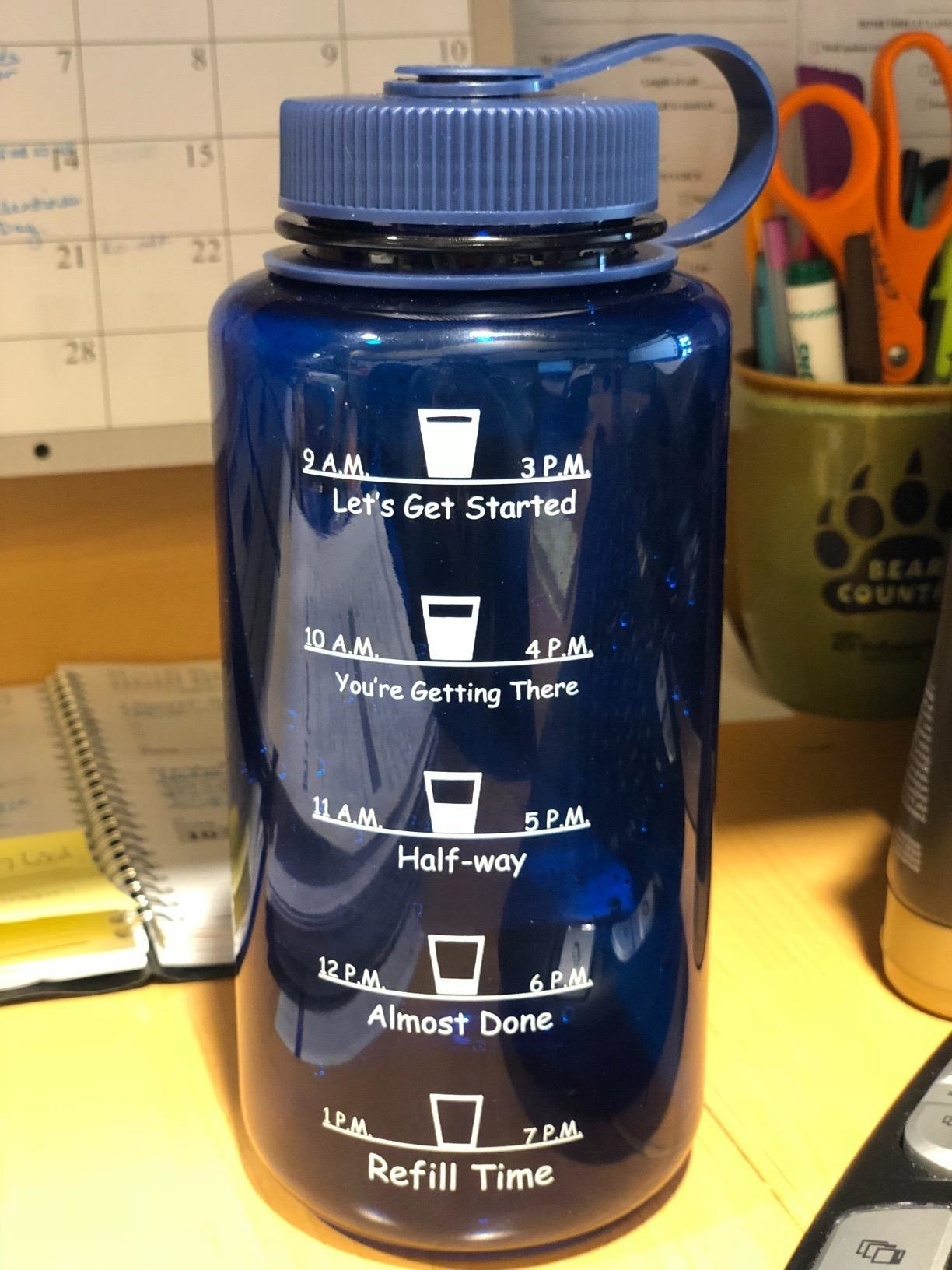 """Reviewer photo of blue time-marked water bottle placed on desk with times ranging from 9 AM to 7PM and text that reads """"Let's Get Started,"""" """"You're Getting There,"""" """"Half-way,"""" """"Almost Done,"""" and """"Refill Time"""""""