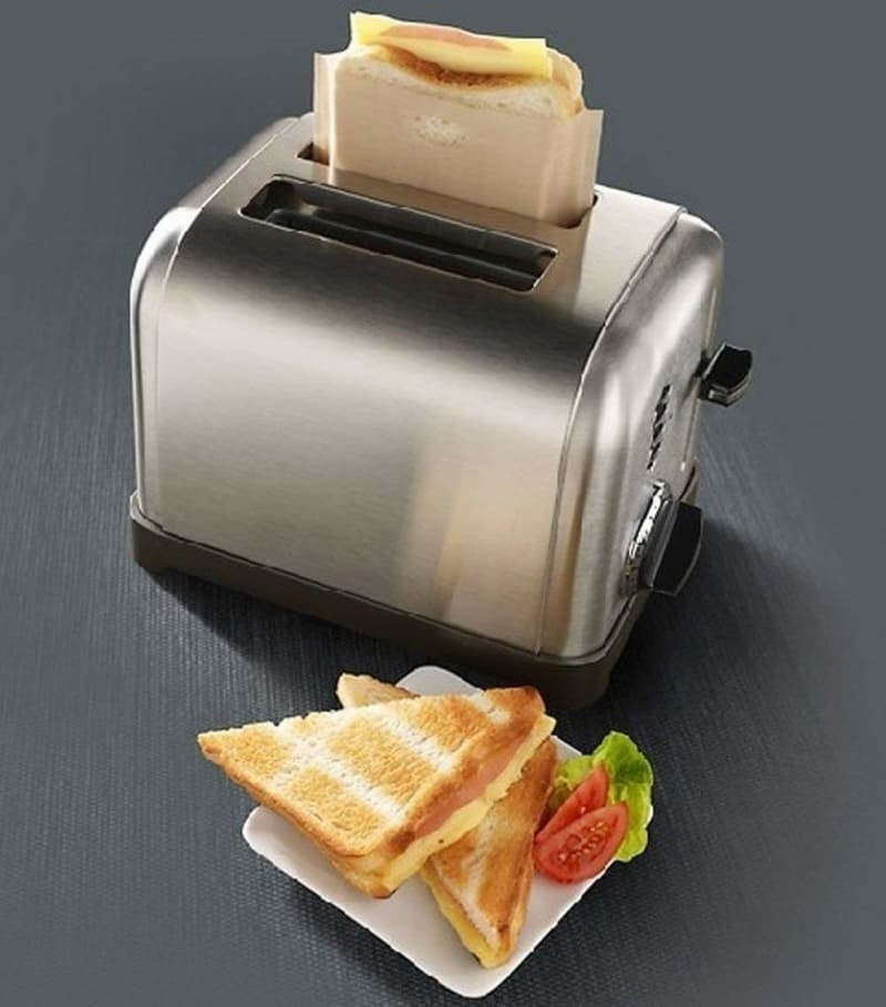 Product shot of heat-resistant toaster bags in a toaster sitting next to a grilled cheese