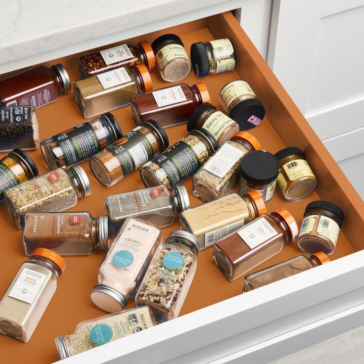 A drawer with scattered spice bottles on their sides