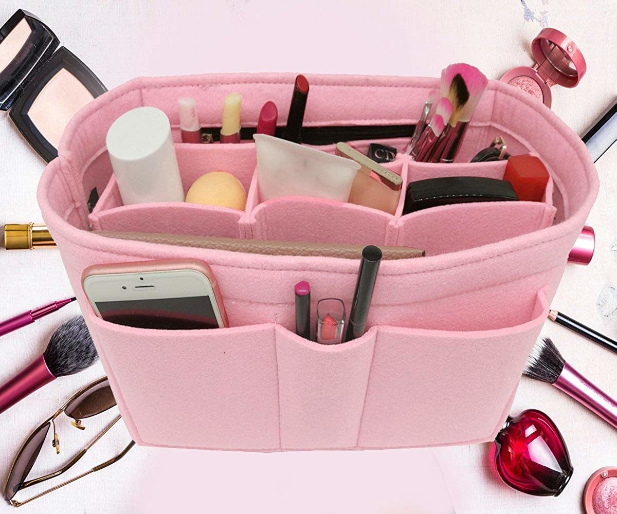 The organizer filled with items, including makeup brushes, phone, beauty products, and more