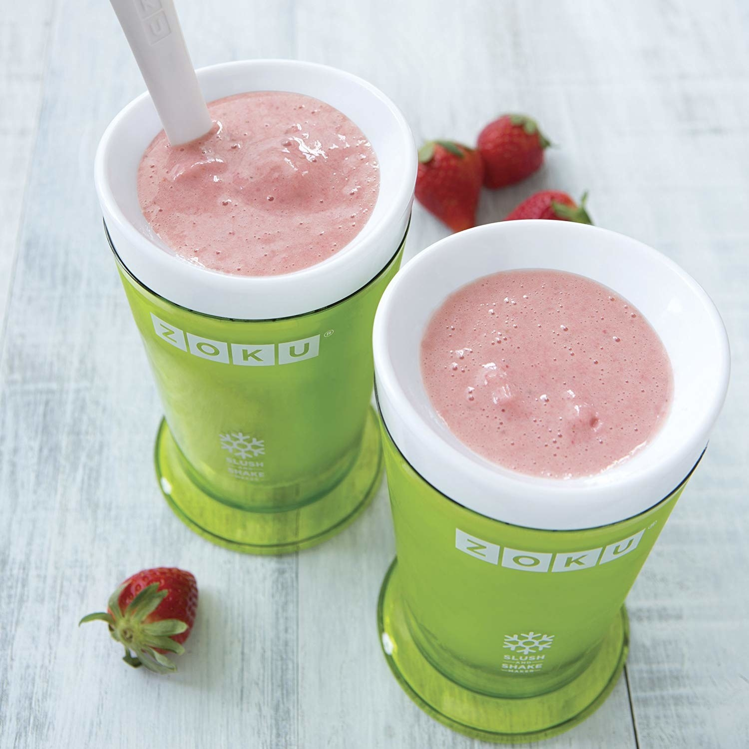Two green, tall cups with pink strawberry smoothie in them that looks slush-like