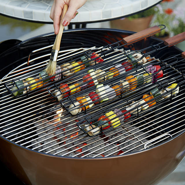 Kabob baskets on the grill with different veggies inside and a hand brushing oil over them