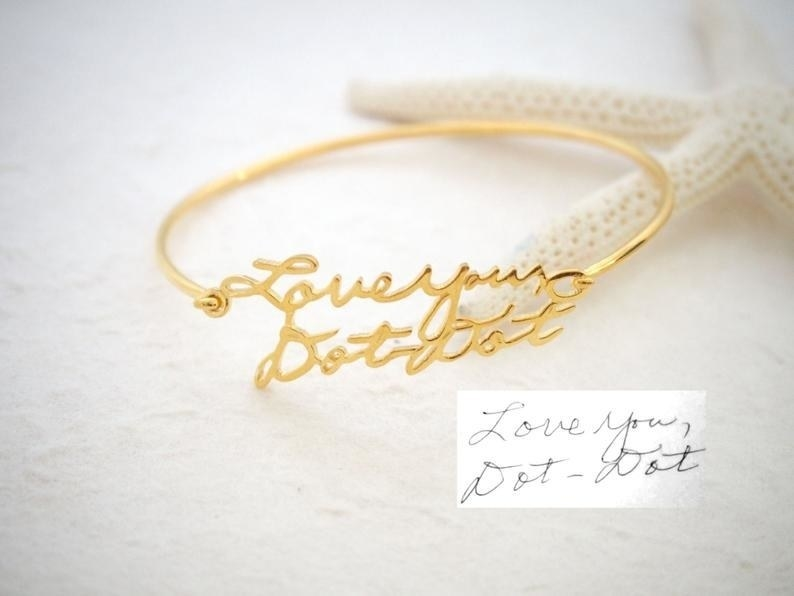 """Gold bracelet with handwriting that spells out, """"Love you, Dot-dot"""""""