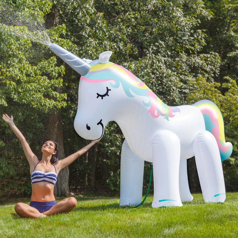 Person sitting in grass under the giant unicorn sprinkler