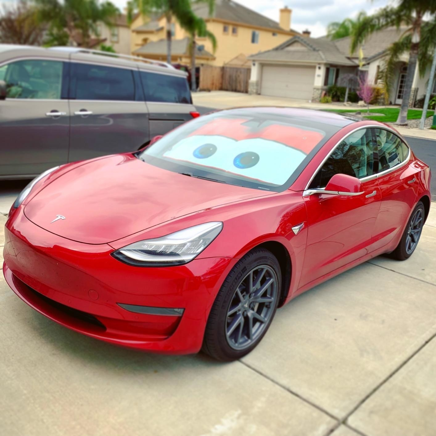 A reviewer's red car with the Lightning McQueen eyes shade in the windshield