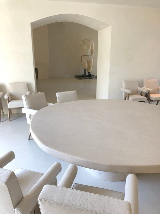 Very minimalist table and chairs with a creepy statue in the back