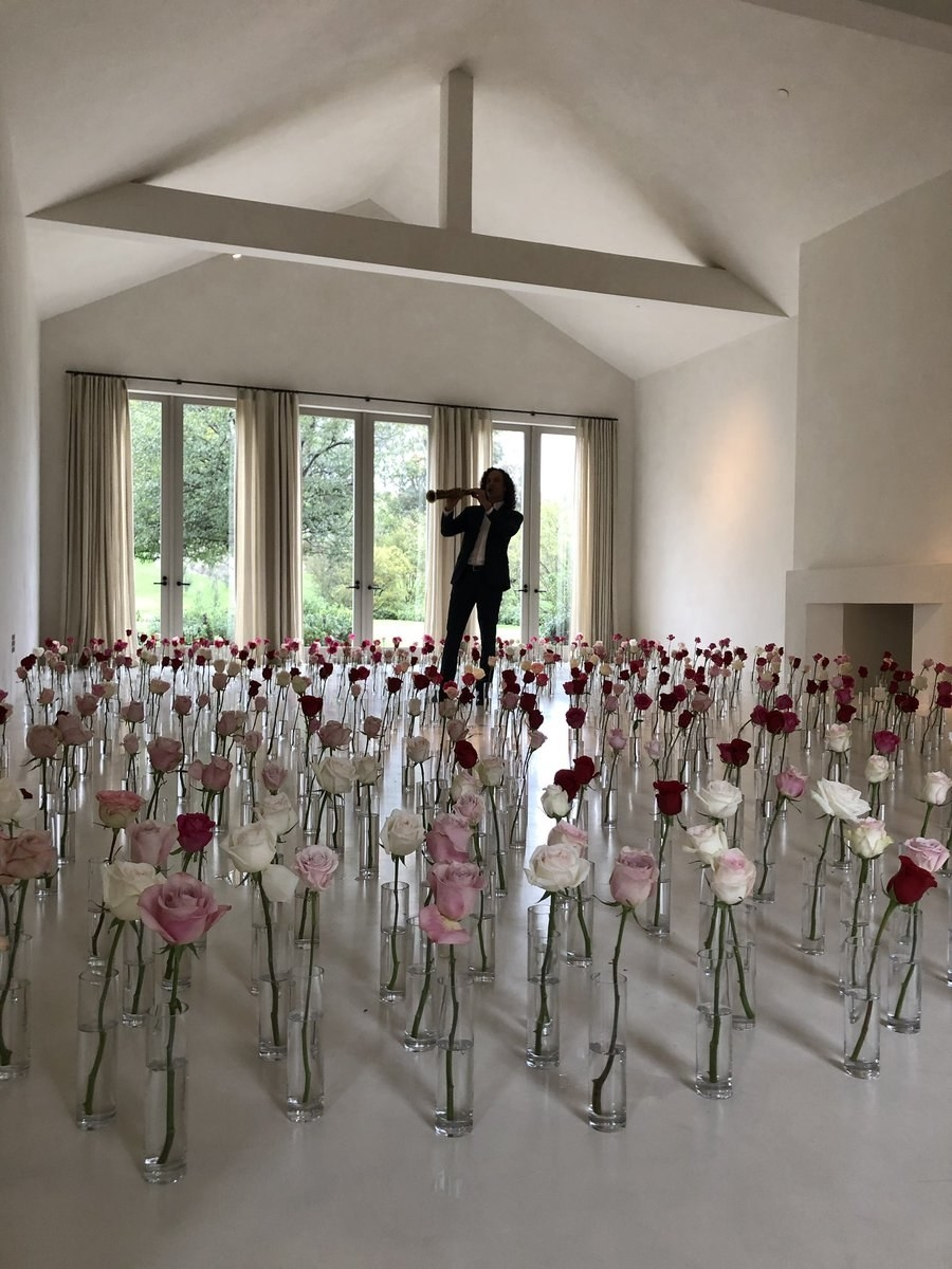 individual roses in individual vases all over the floor as Kenny G plays