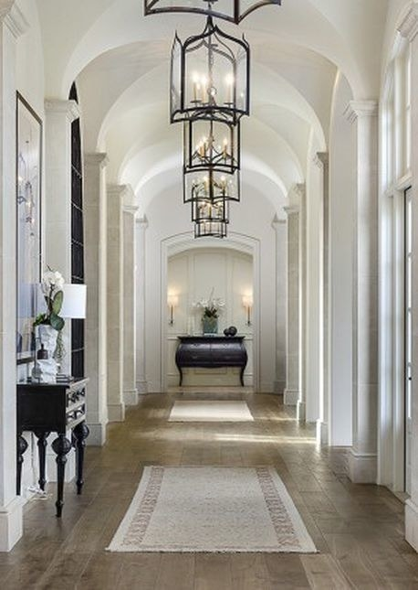 A chandelier hands from the ceiling, two rugs on the floor, and decorative tables line the hallway