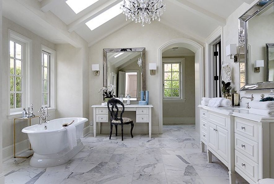 a large mirror, a fancy bathtub, and marble floors