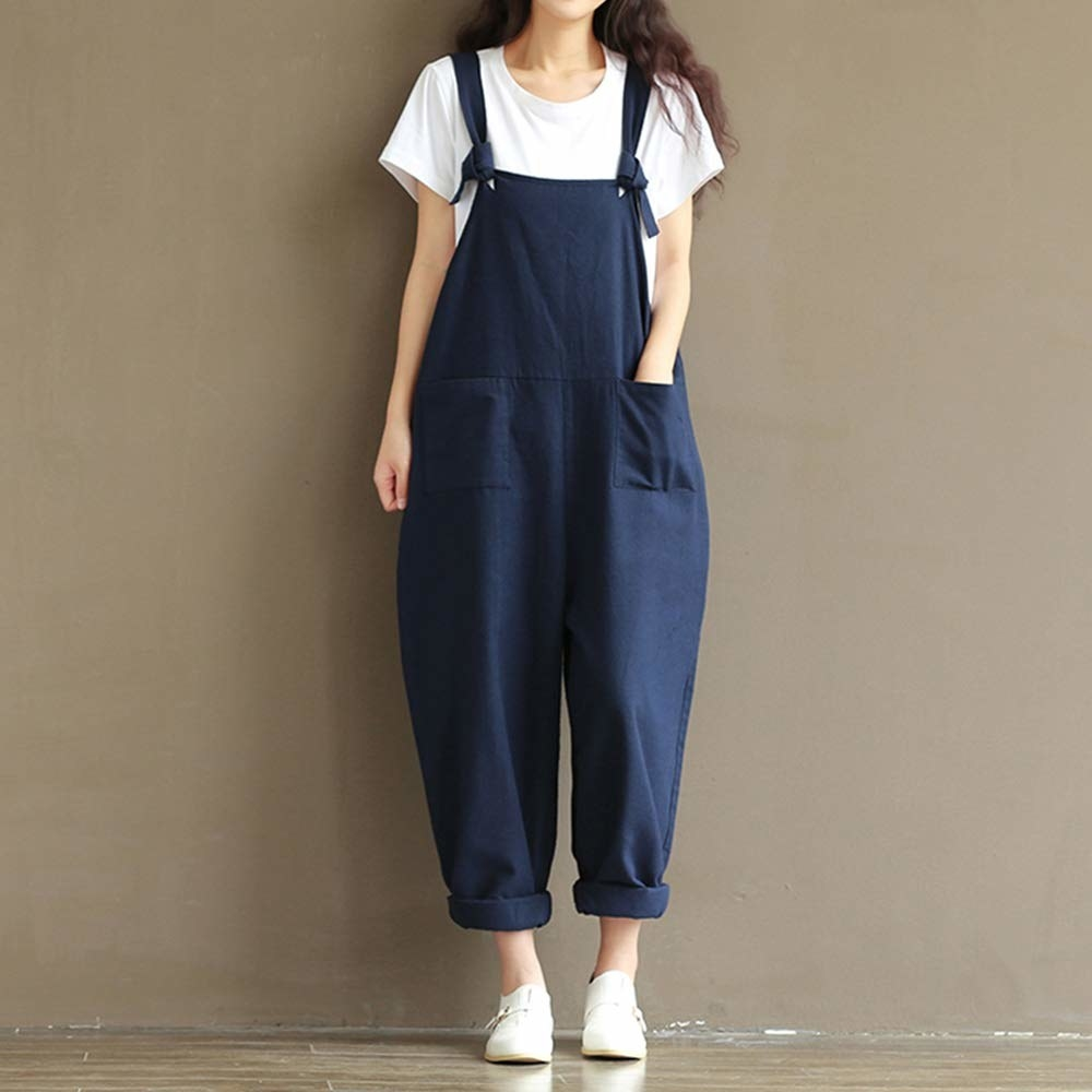 Model wearing the overalls in navy over a white tee