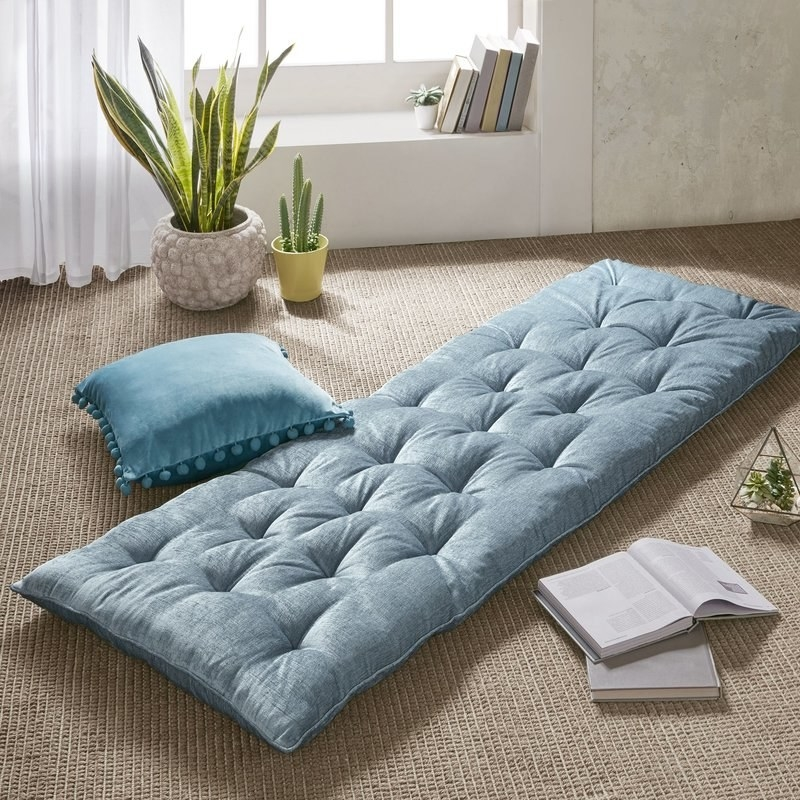 light blue tufted pillow on a floor