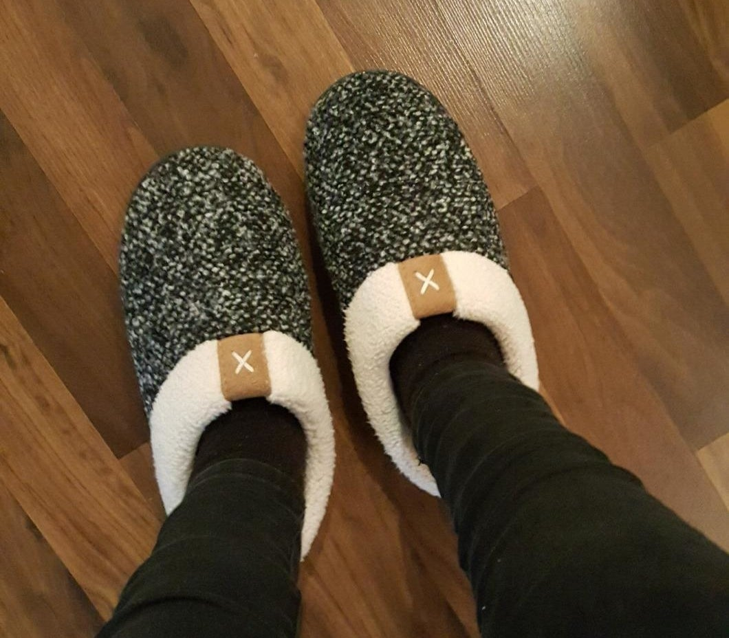 reviewer wearing the slippers which have a white and black speckle pattern and a white sherpa lining