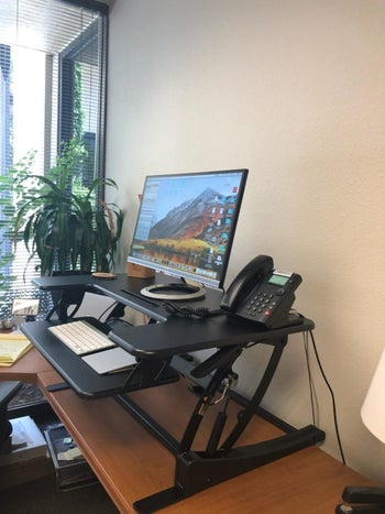 Same reviewer's photo of their desk but it's lifted, allowing them to work standing