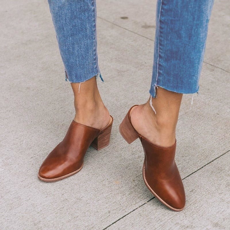 Model wearing the rounded toe mules with a chunky heel in brown