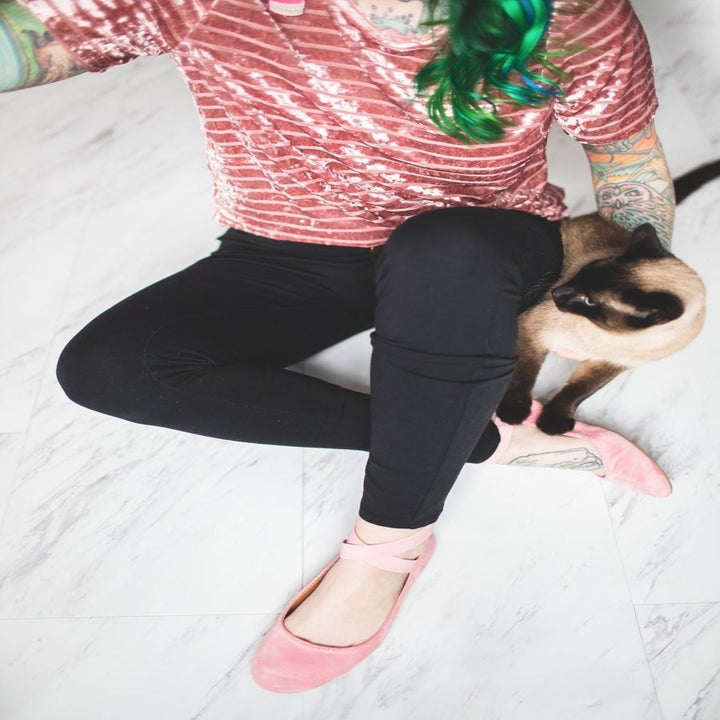 reviewer wearing the shoes with criss-cross straps across the ankle in pink suede