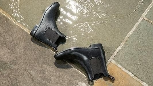 The rain boots with a u-shaped patch of elastic on either side, slight heel, and pull tab on the heel in black lying on the ground