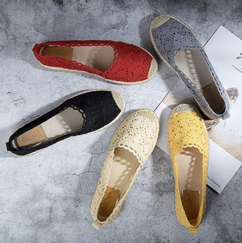 Five single espadrilles in different colors with a lace-like fabric