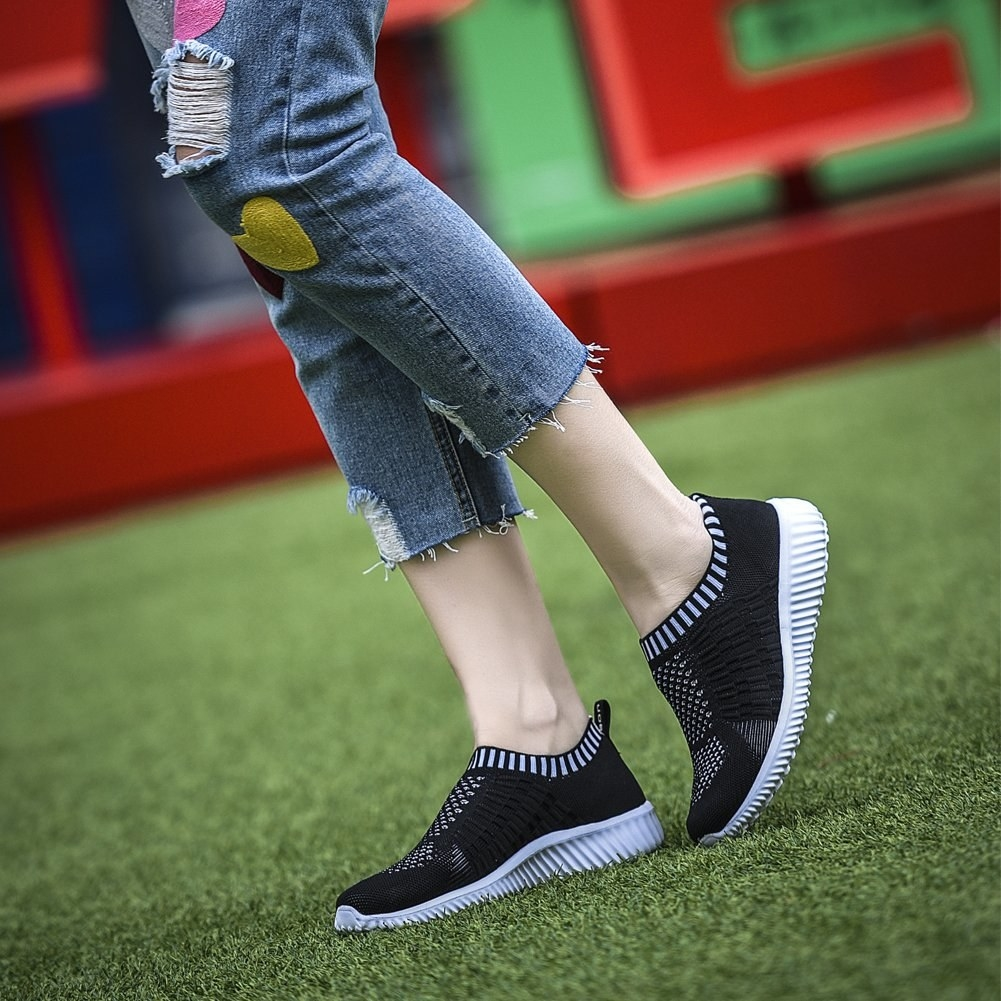Model wearing the sneakers with a knit design in black and white