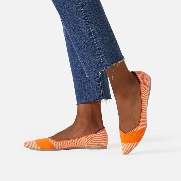Model wearing the pointed toe flats with an orange stripe across the top and small orange and white stripes around the rest of the shoe