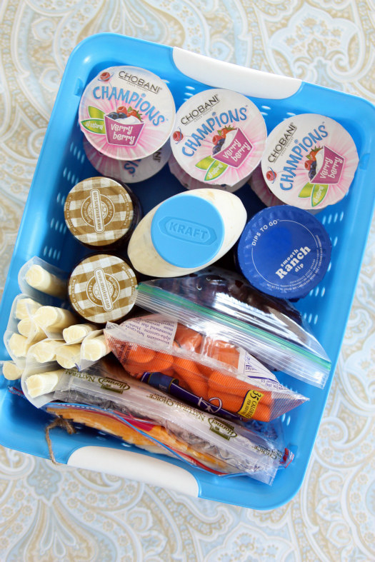 Blogger photo of a plastic bin with snacks like carrots and cheese sticks in it