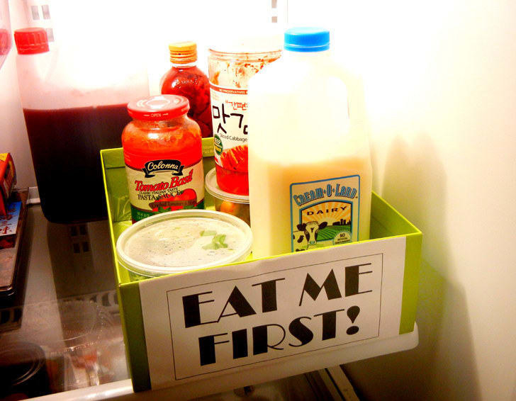 """Box labeled """"Eat me first!"""" sitting in the fridge filled with foods that will spoil soon"""