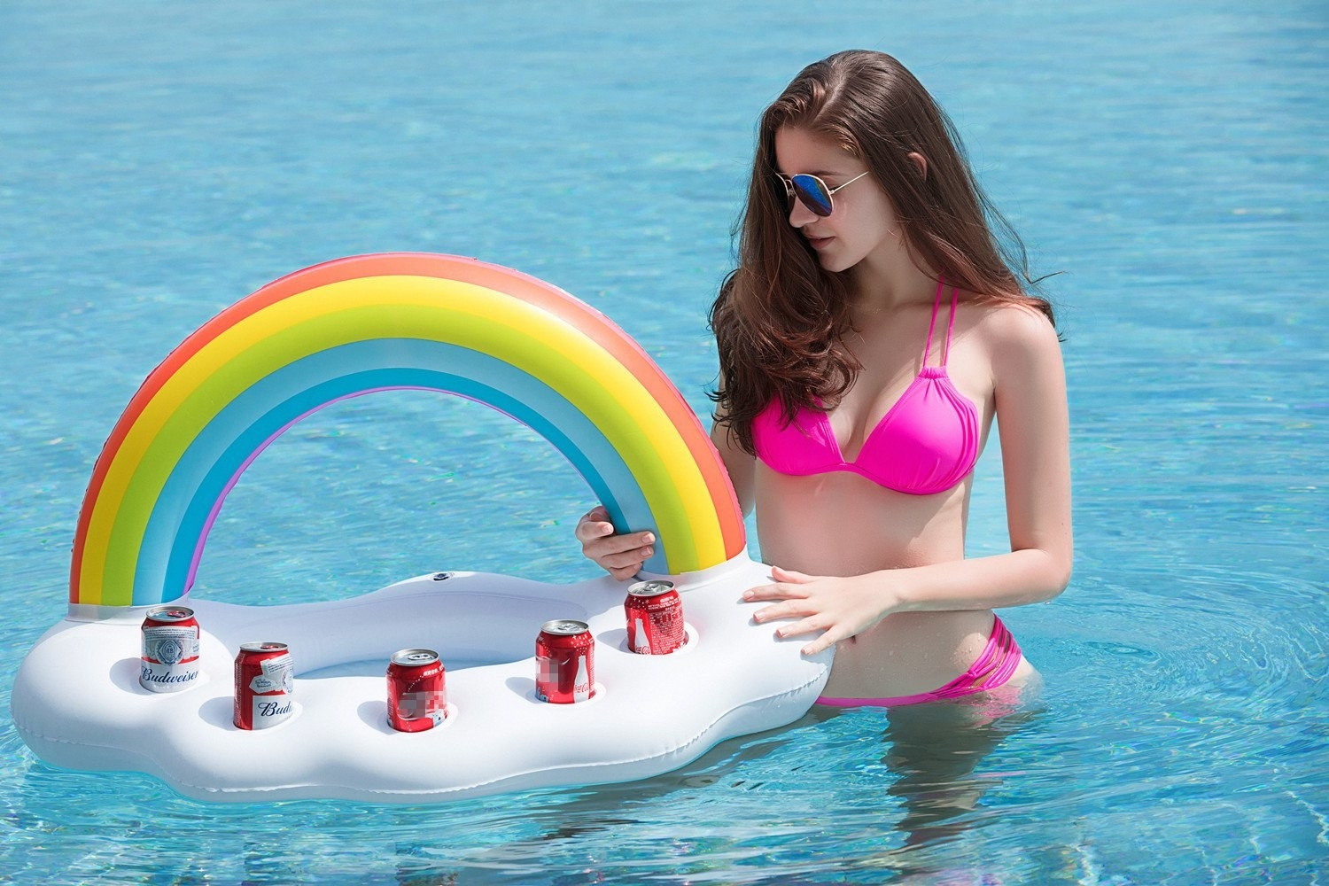 a model in the pool holding on to the floating bar that is shaped like a rainbow with a cloud to hold drinks