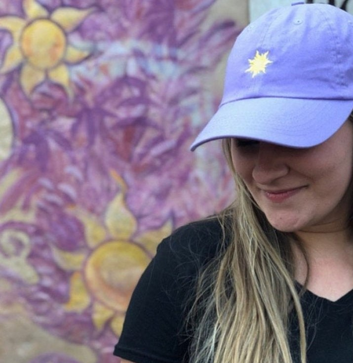 a model wearing a purple hat with the tangled sun icon on it