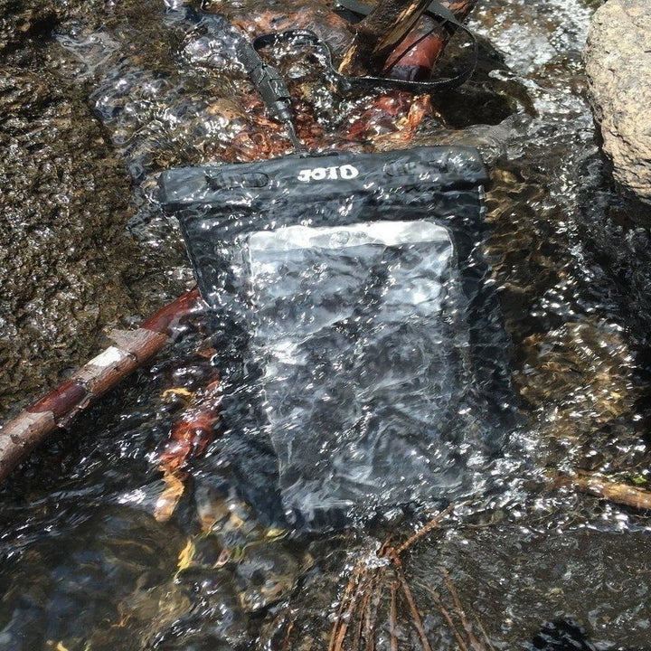 A reviewer's phone in the case, submerged in a stream