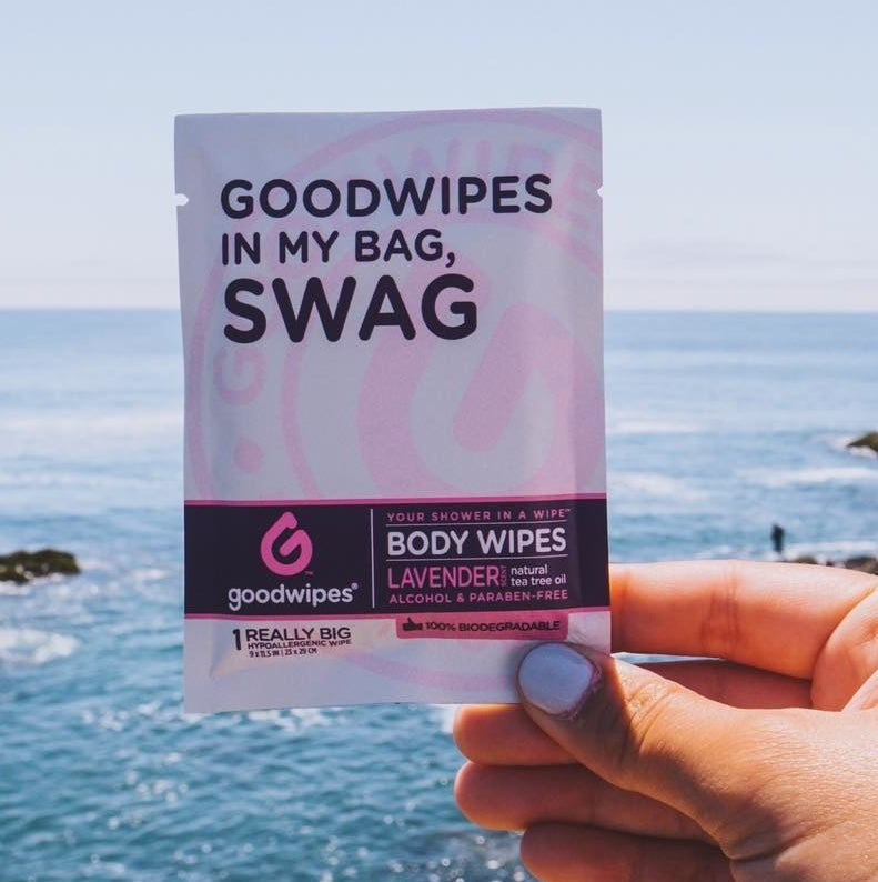 "Hand holding purple wipe packet with the words, ""Goodwipes in my bag, swag"""